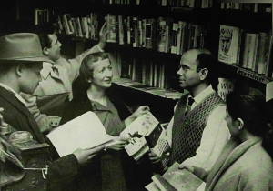 James Rigberg (in sweater and tie to the right) in his bookstore, featured in an article in the Saturday Evening Post in 1956. Image from John Kobler,
